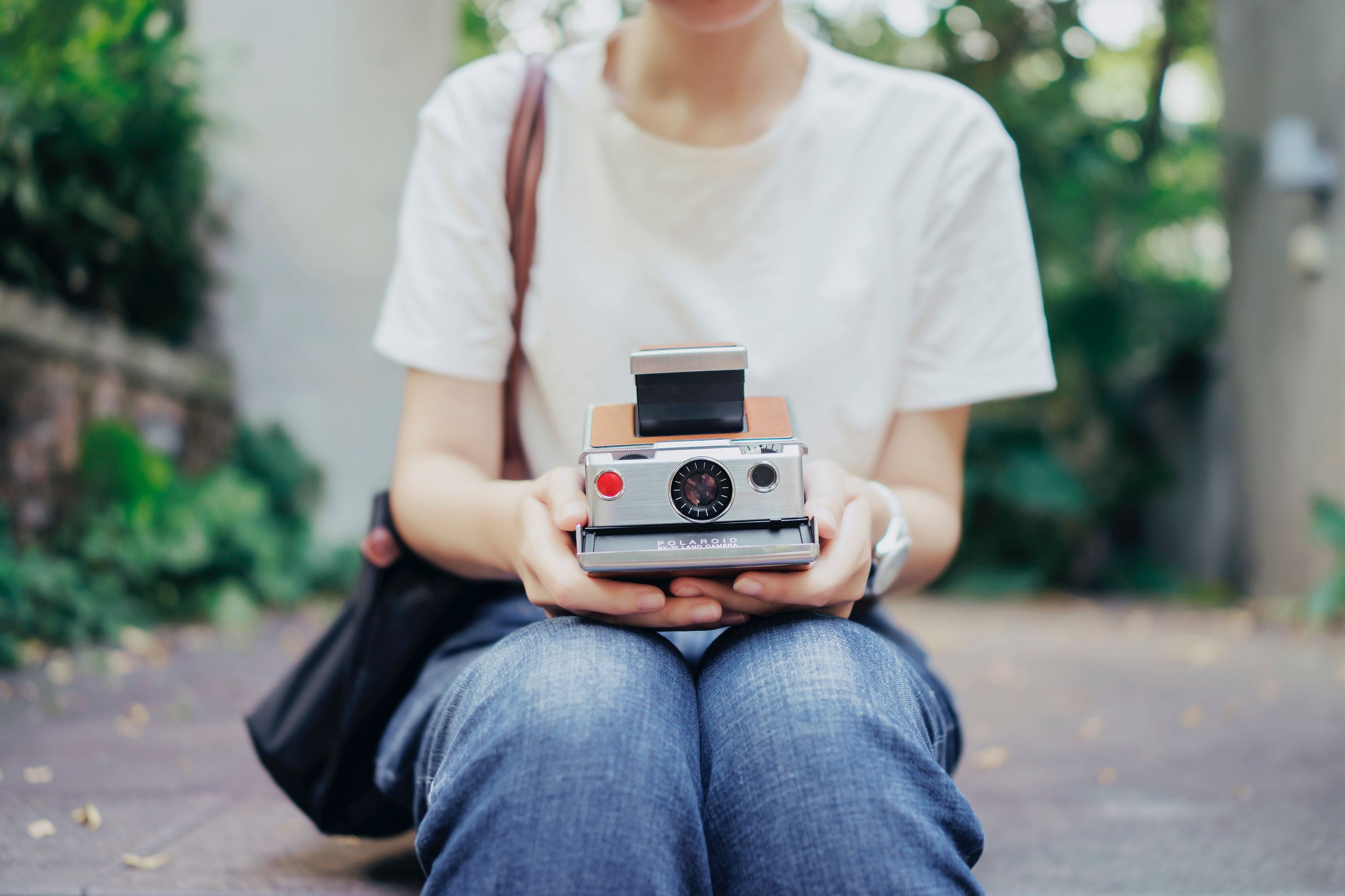 Slow Tech: woman holding polaroid camera